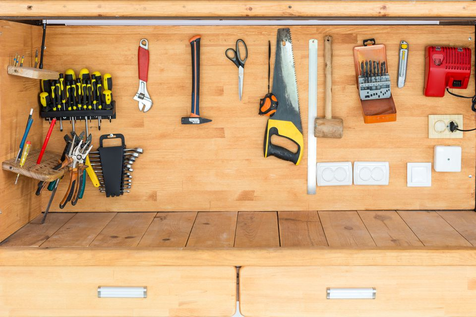 Wooden workbench at workshop. Lot of different tools for diy and repair works. Wood desk for product display. Copyspace. Labour day