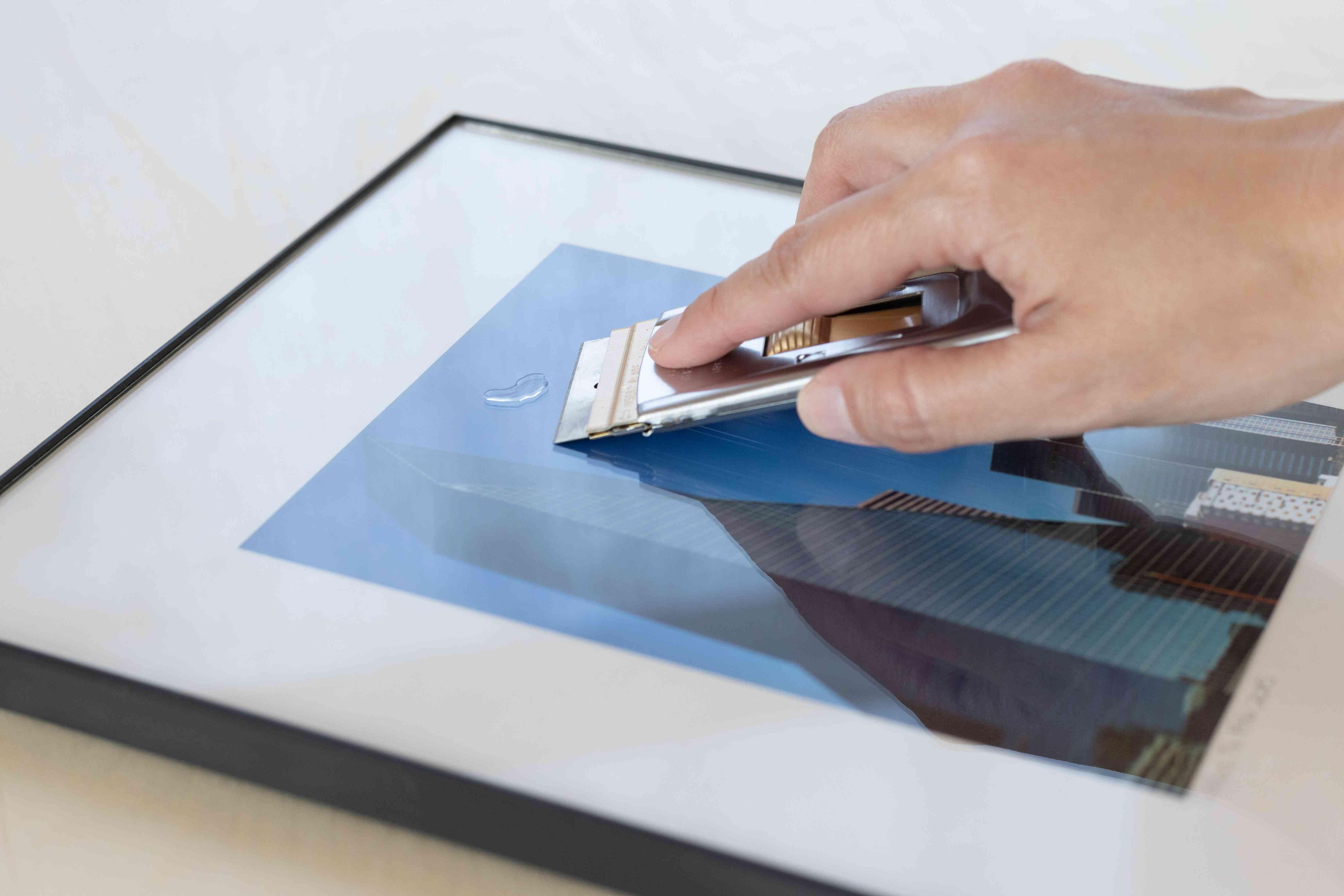 Safety razor scraper peeling off super glue from picture frame