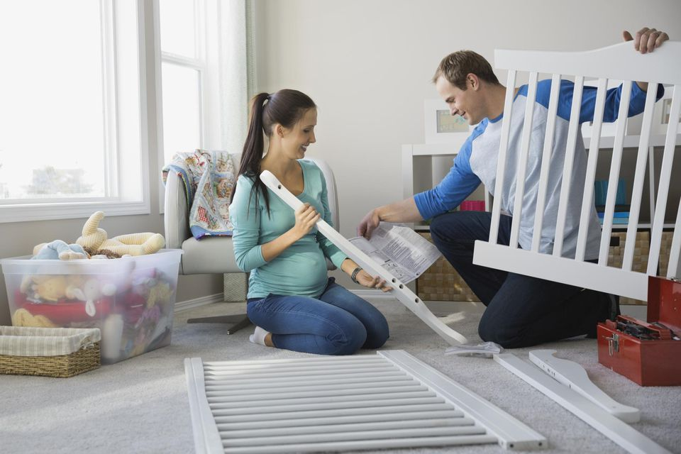 Expectant couple assembling crib together