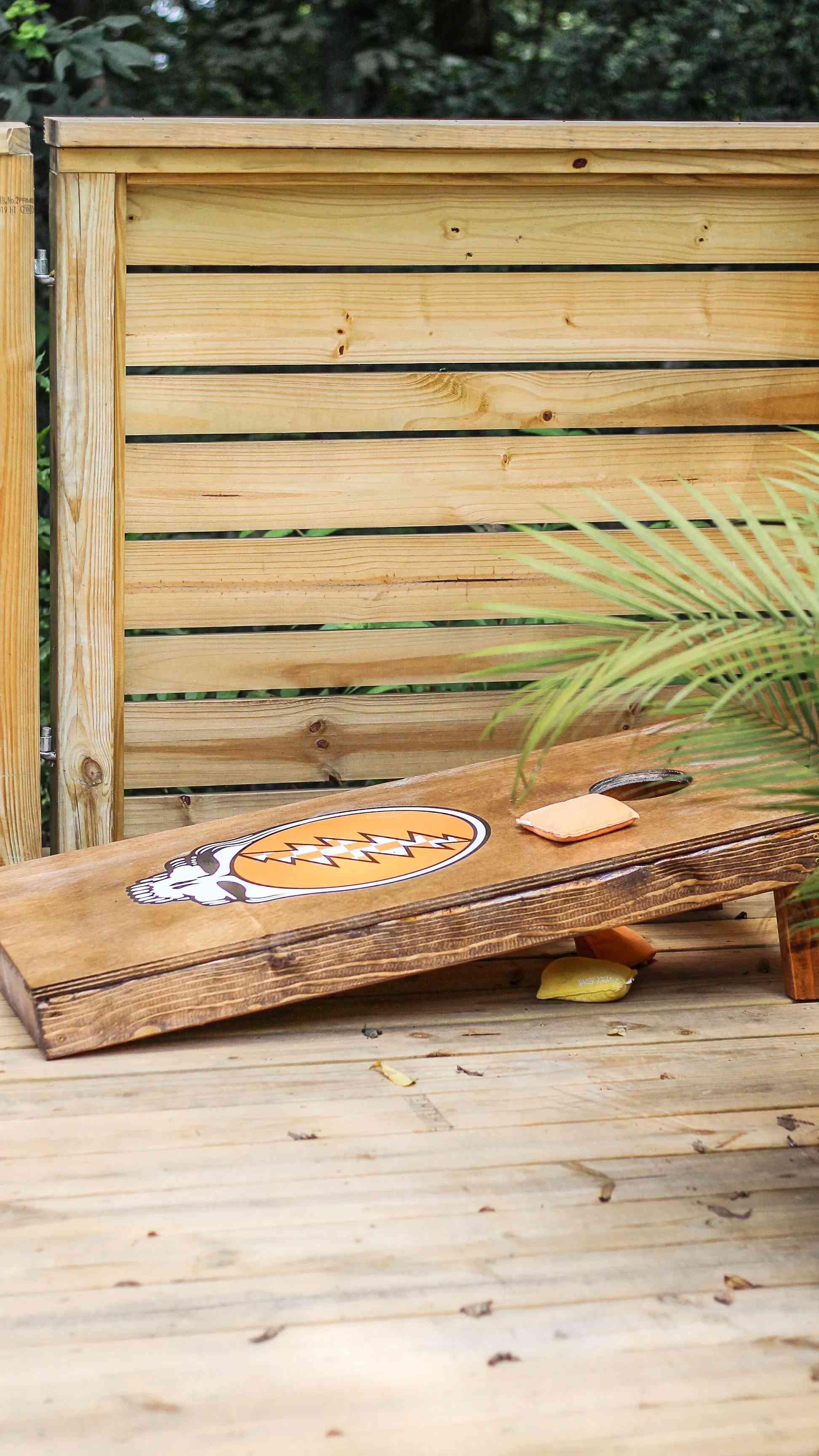 A wooden cornhole board on a deck