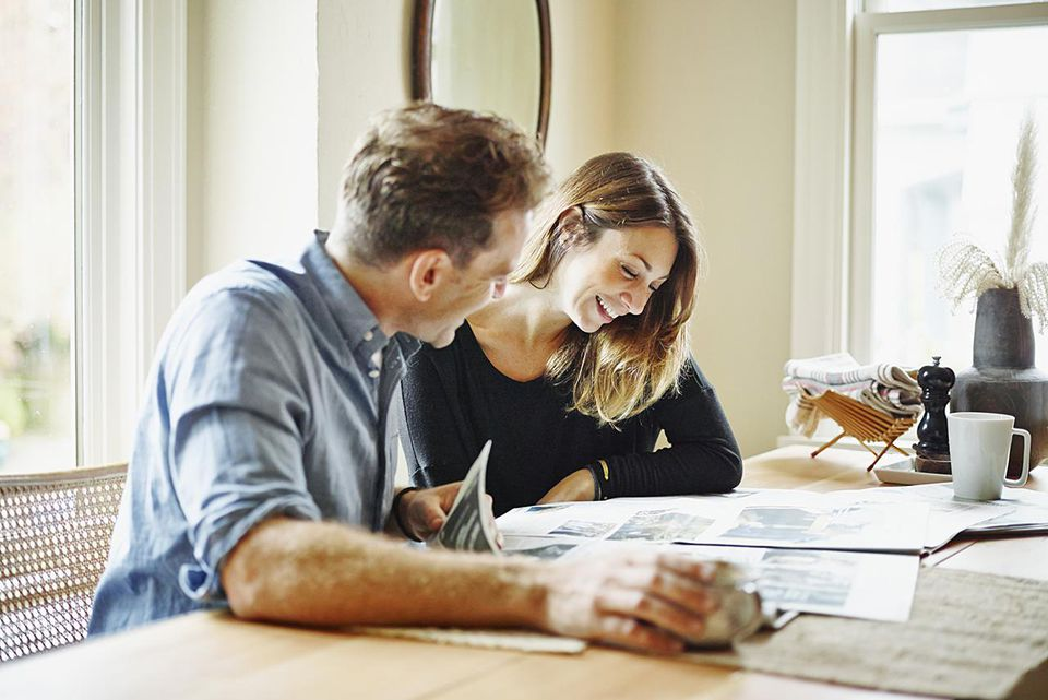 Smiling couple sitting at table in home reading newspaper together