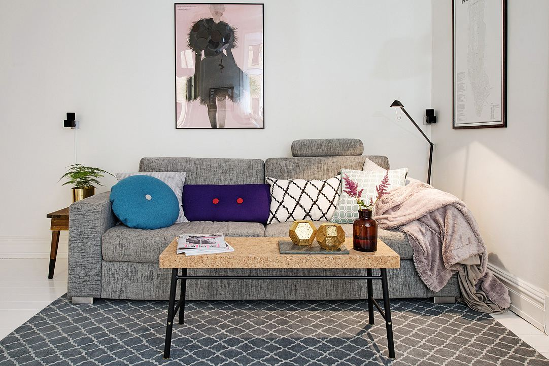 Cozy room with a gray couch, coffee table, gray rug, and artwork