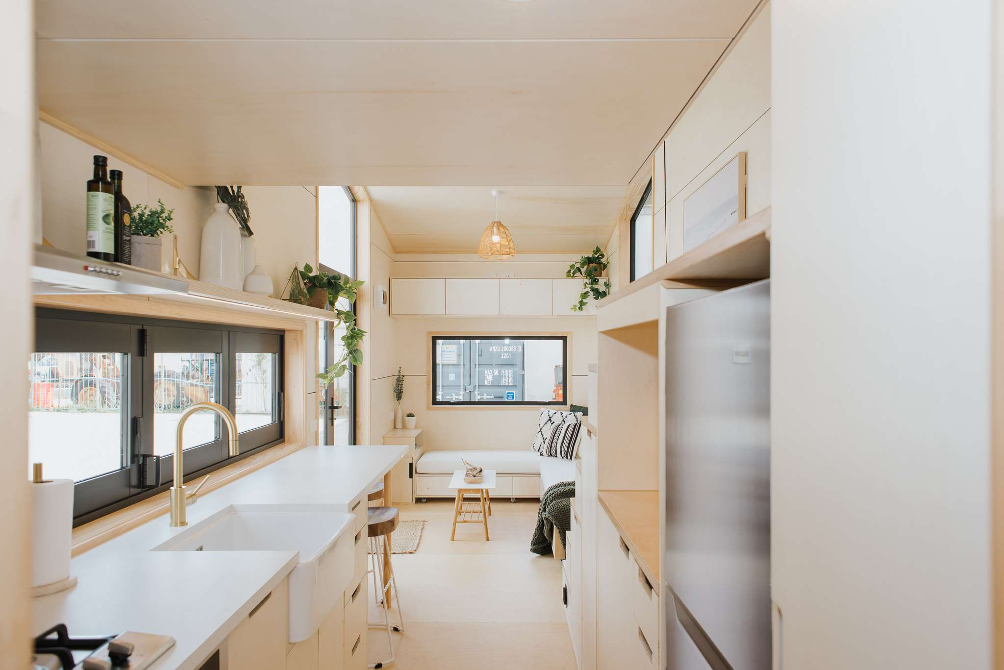 a tiny home kitchen with light wood and clean lines