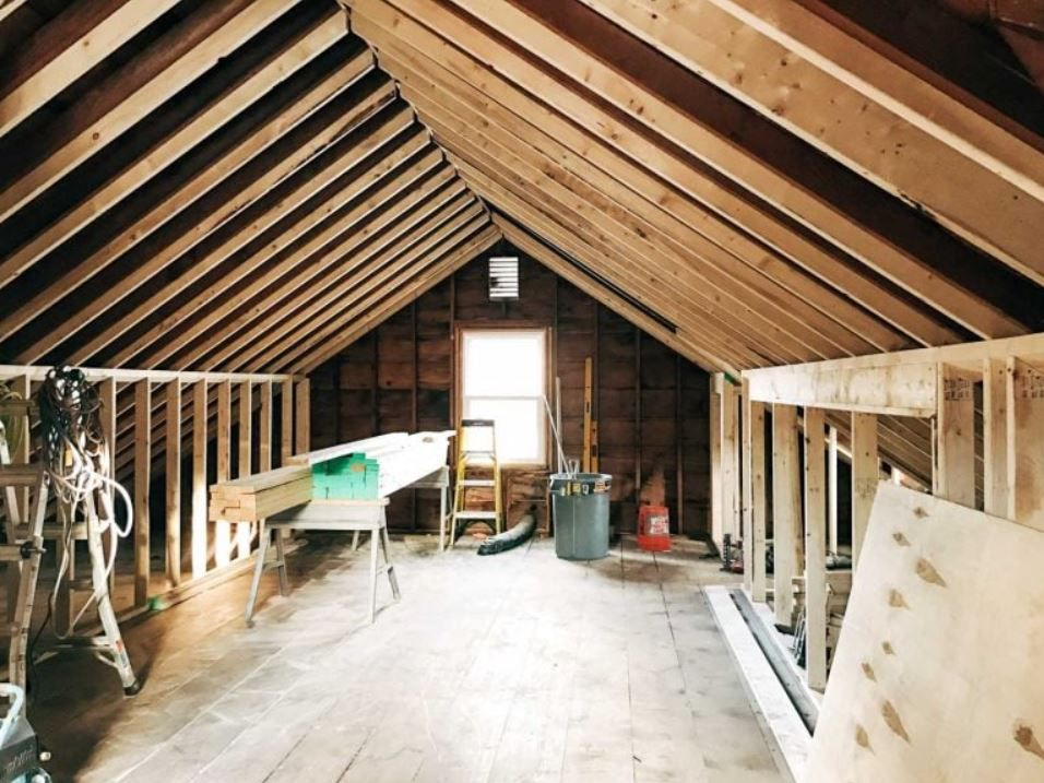 Unfinished attic space with exposed wood walls and ceiling.