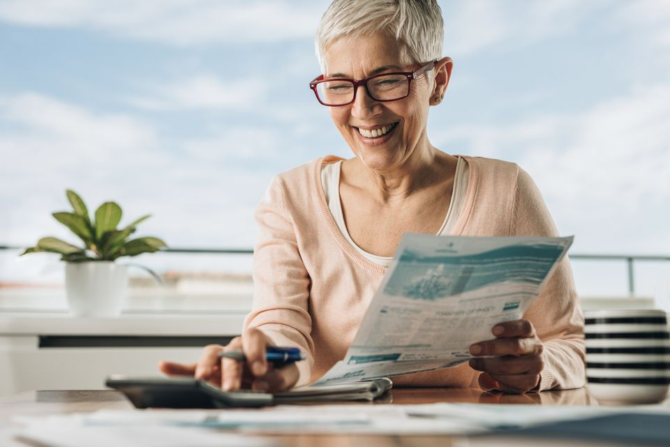 Happy mature woman using calculator while going through home finances.