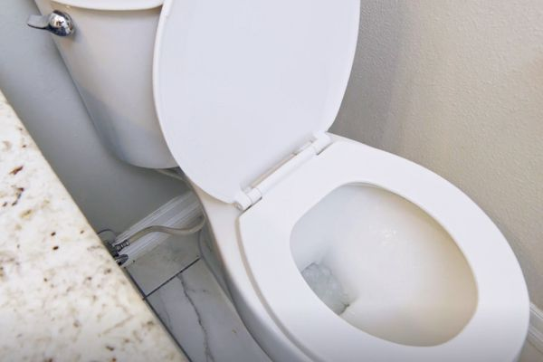 White ceramic toilet with lid open and pipes underneath