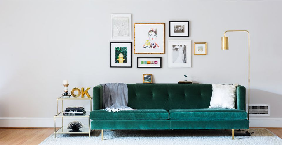 Living room with artwork on wall over teal couch