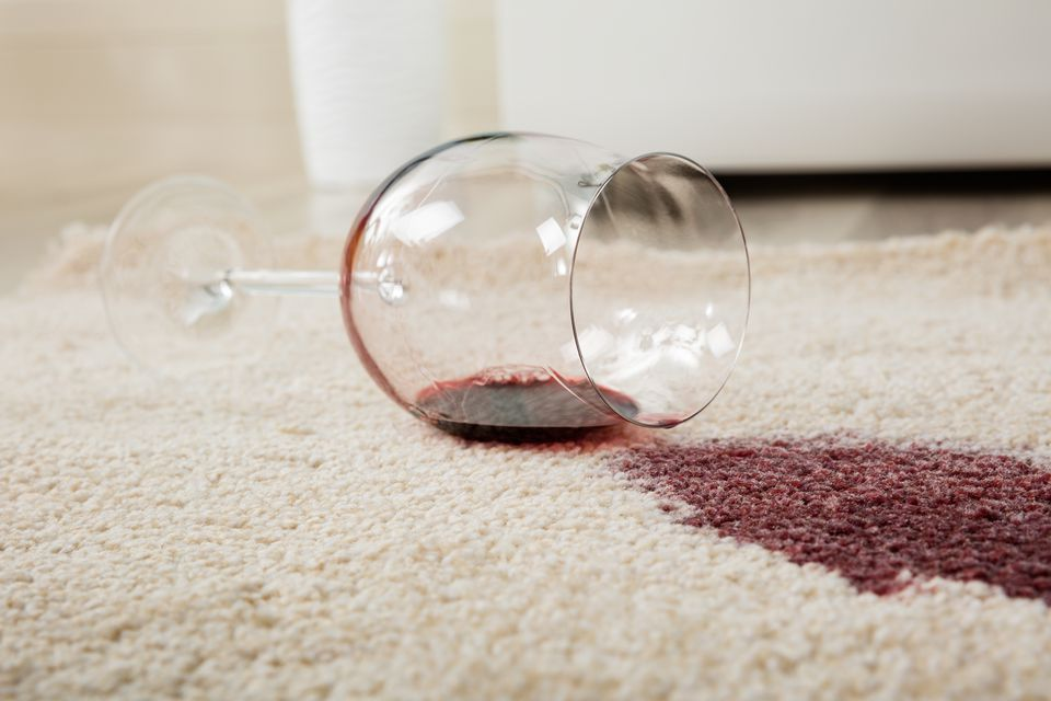 Red wine spilled from a glass onto a carpet