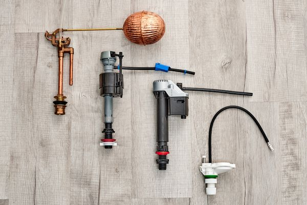 Four different types of toilet fill valves on wooden surface