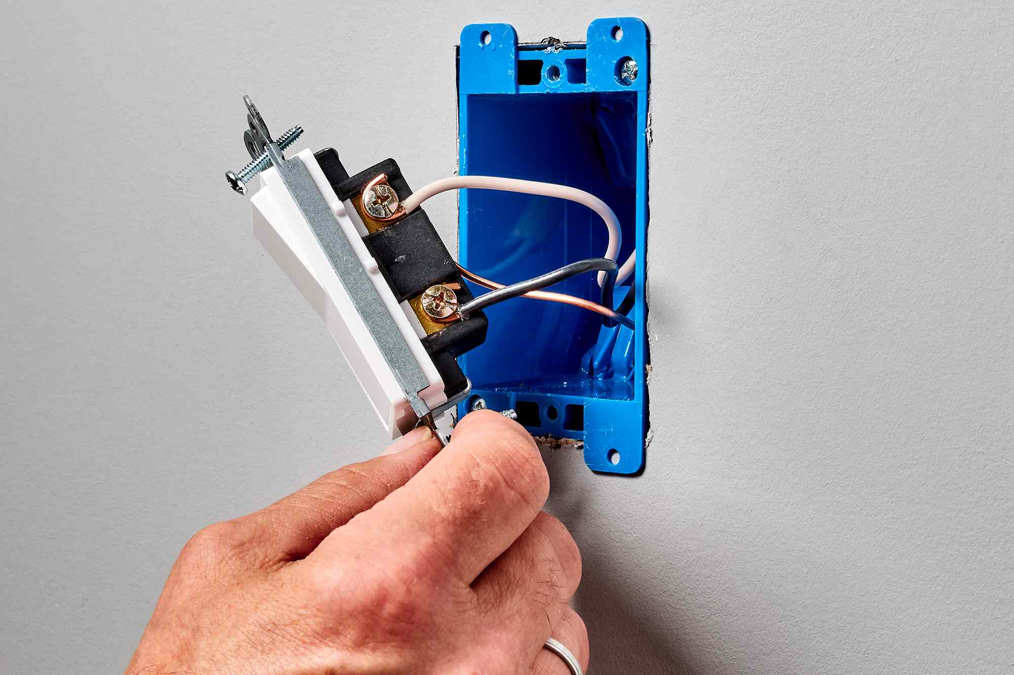 Wires wrapped on side of switch with grounding screws being examined