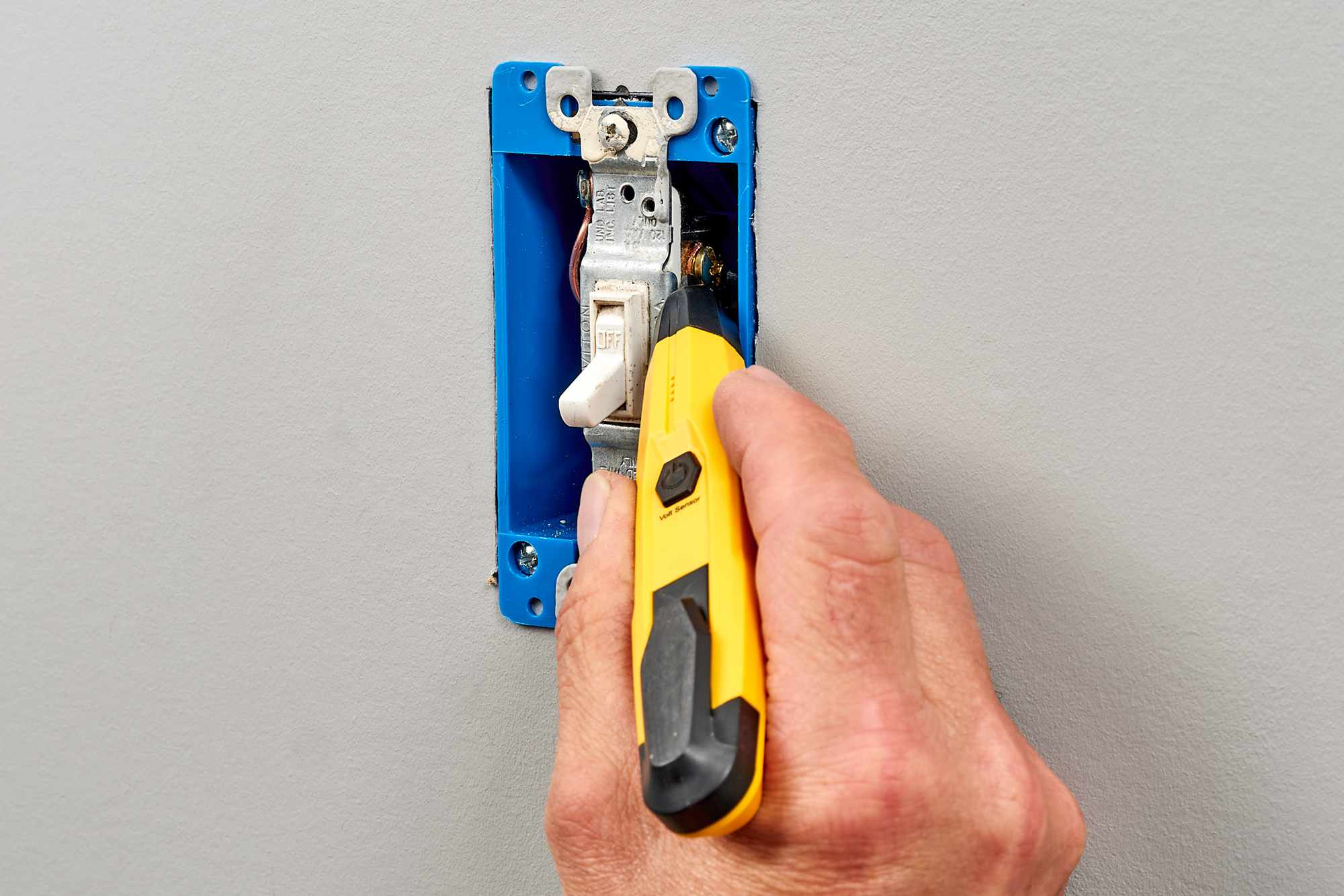 Yellow non-contact voltage tester inserted into switch box