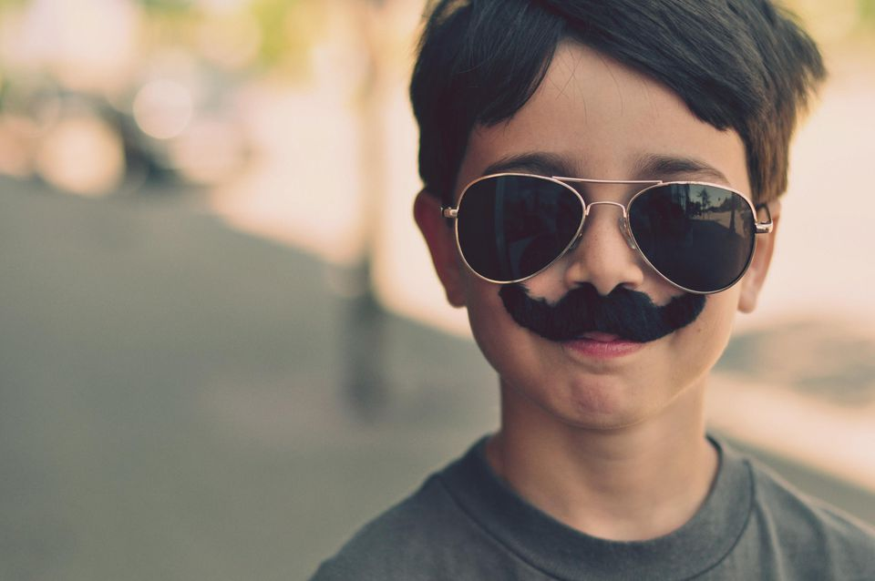 Boy wearing sunglasses and a fake mustache