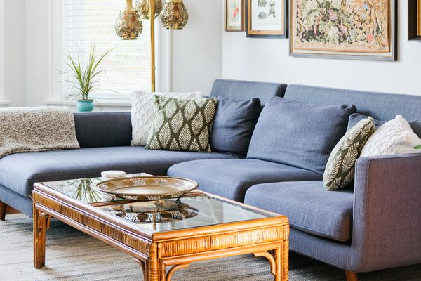 Decorated living room with navy blue couch and rattan coffee table
