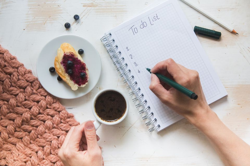 person writing a to-do list with a cup of coffee and pastry