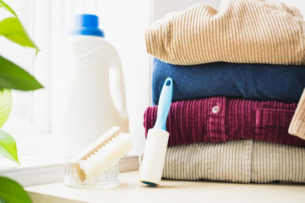 Folded corduroy next to detergent bottle, soft bristled brush and lint roller