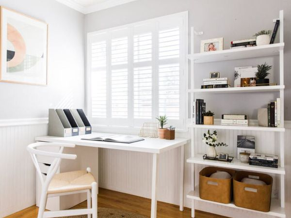 Home office with white desk and bookshelves and open book on desk.
