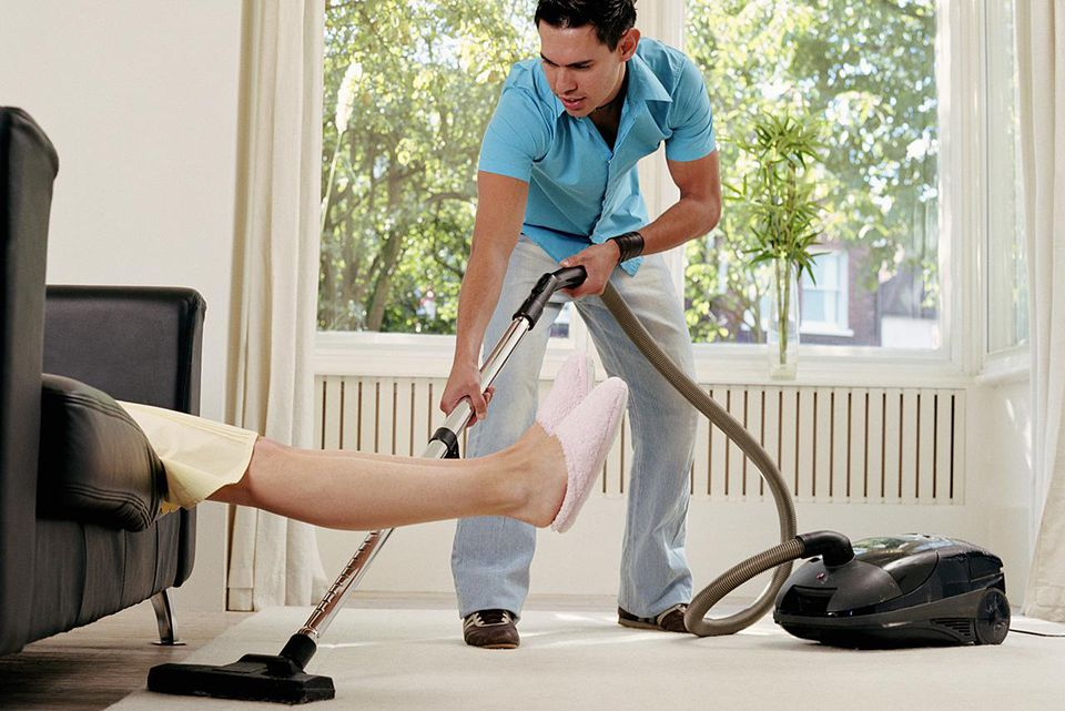 Young man vacuuming rug under woman's legs
