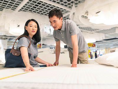 Asian couple measuring a mattress