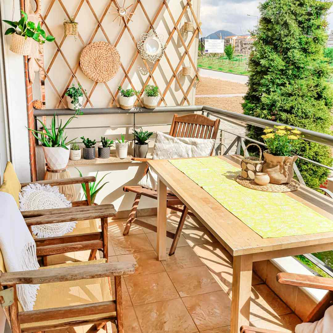 A patio with a dining table, chairs and a lattice filled with potted plants and decor.