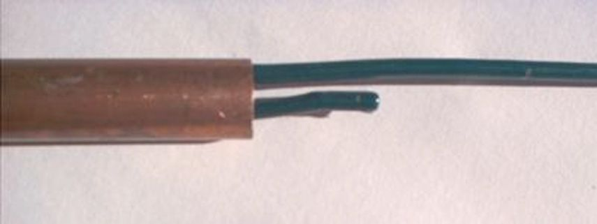 The tip of a rod being jammed up a supporting copper pipe