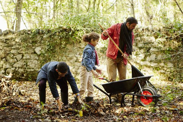 A family raking and scooping up leaves in autumn