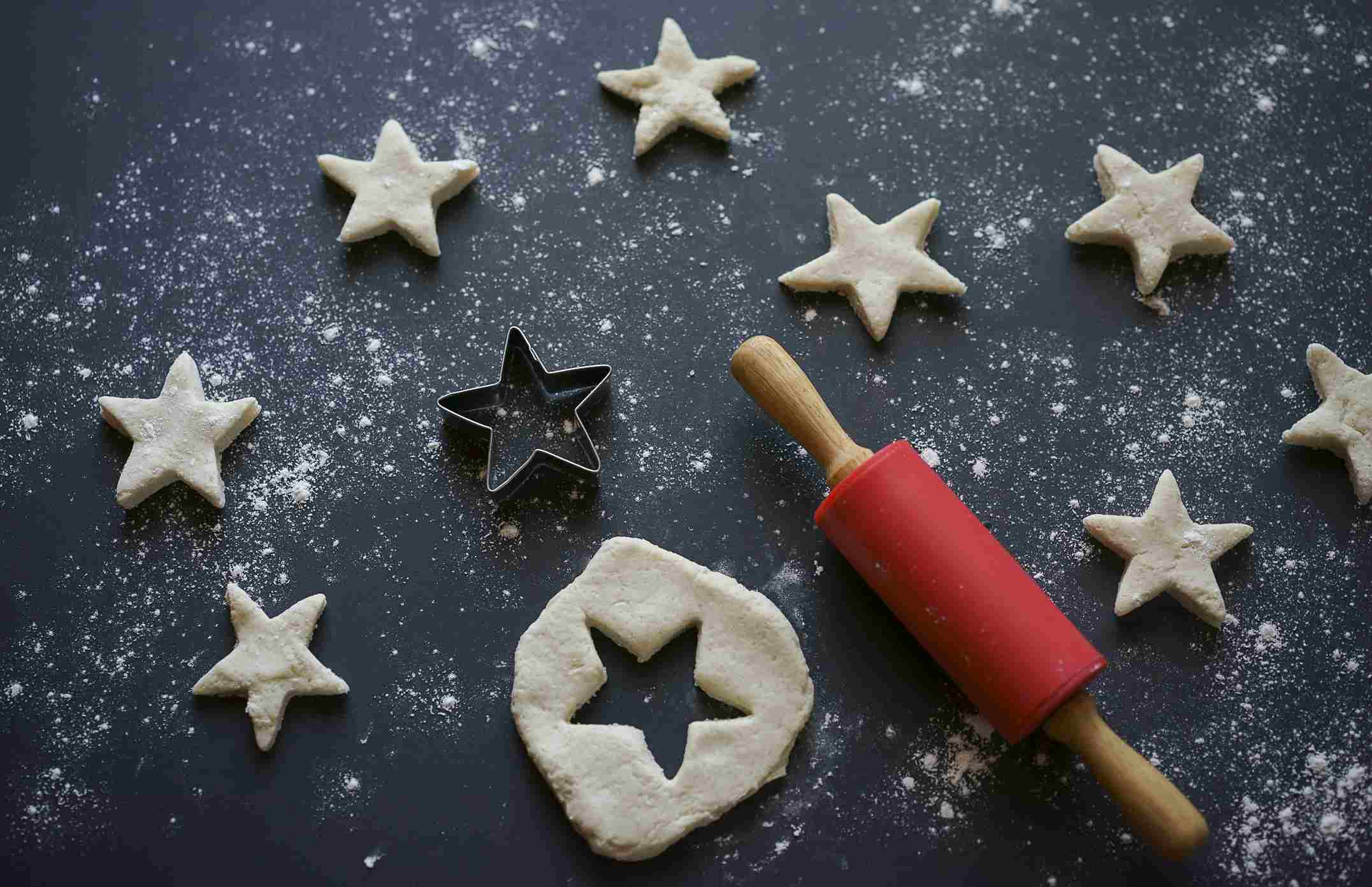 Cookie dough cut into stars with cookie cutting tools