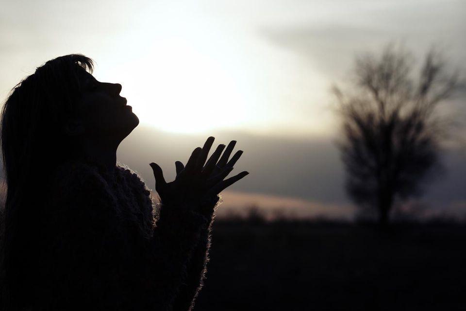 Prayraying woman in field