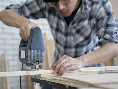 Young carpenter using an electric jigsaw