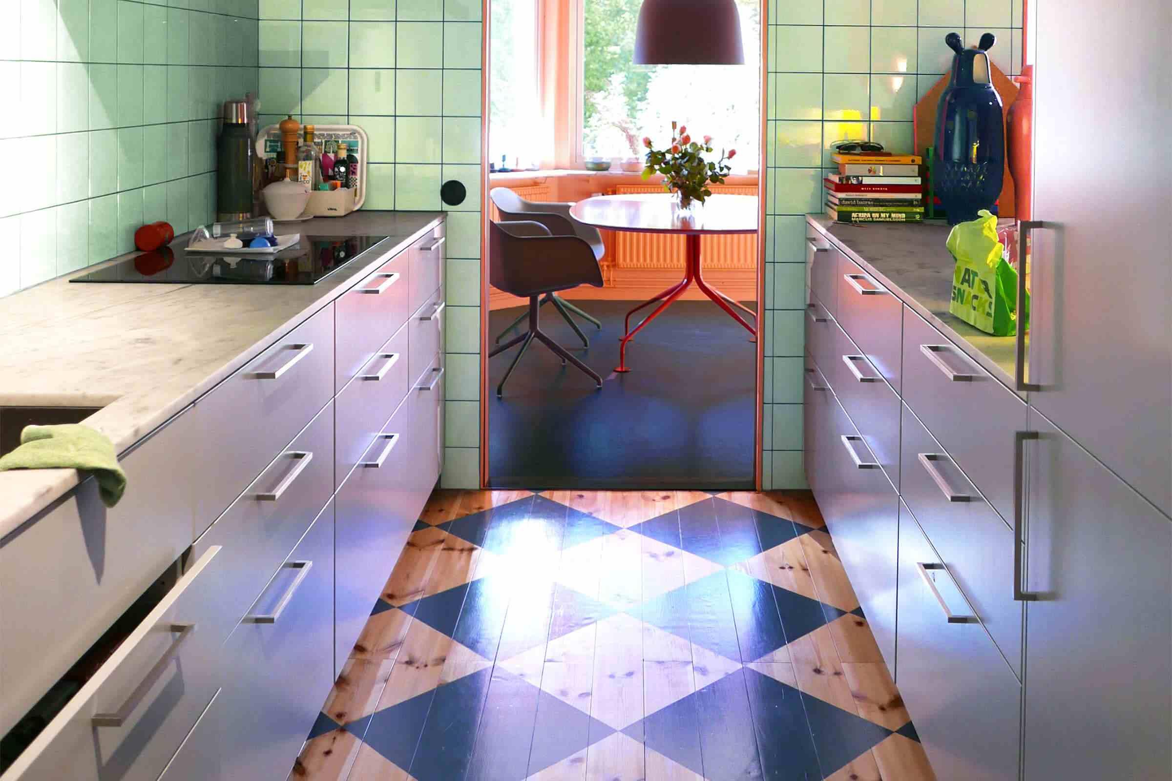 azulejo de cocina verde menta en las paredes y pisos de madera en la cocina