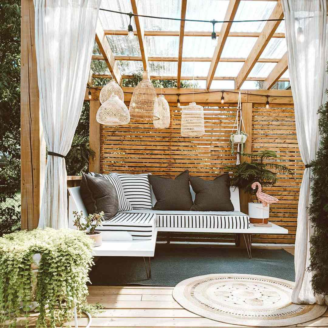 An outdoor room with sheer curtains, hanging pendant lighting and a sectional.