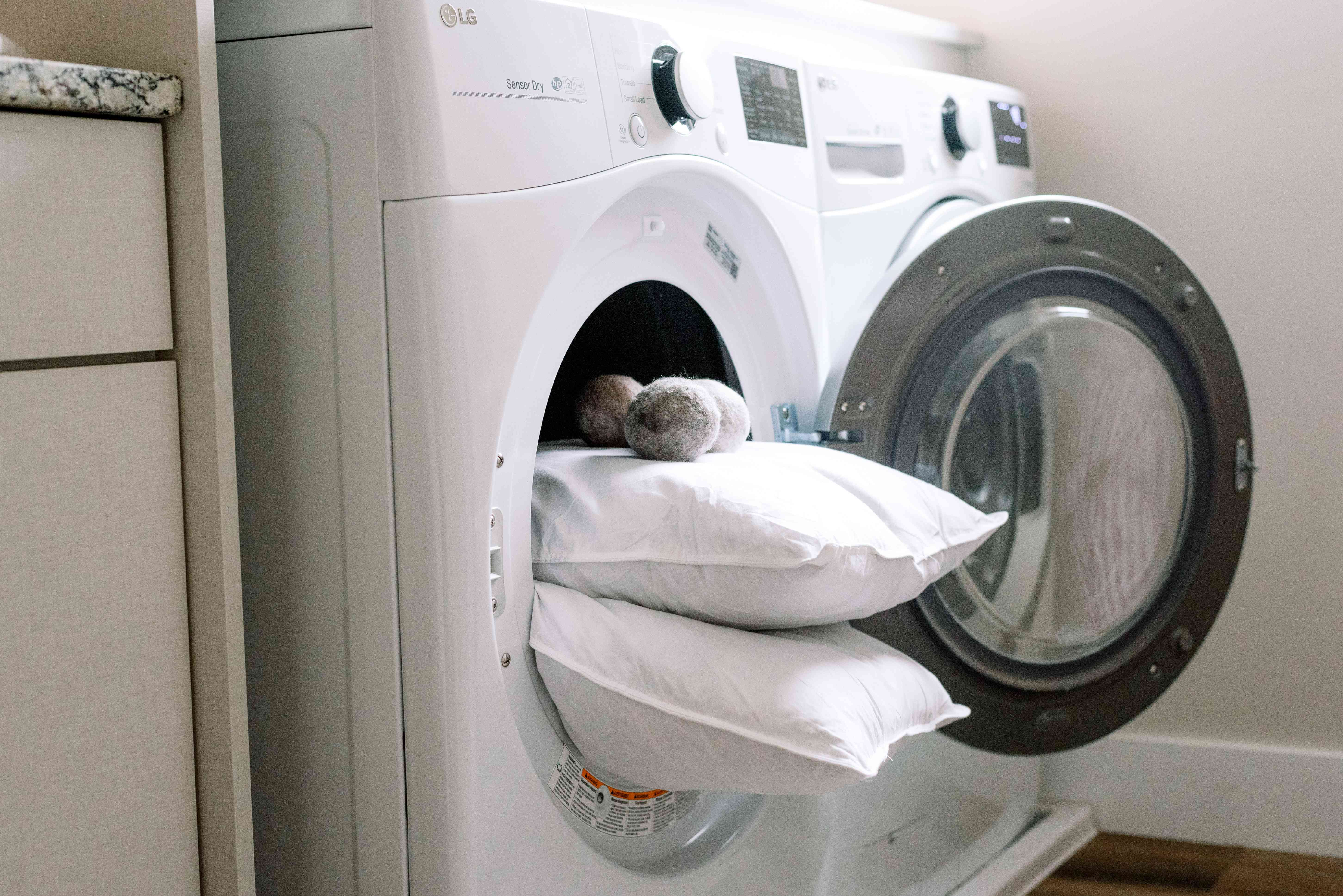 Two pillows and dryer balls in a dryer