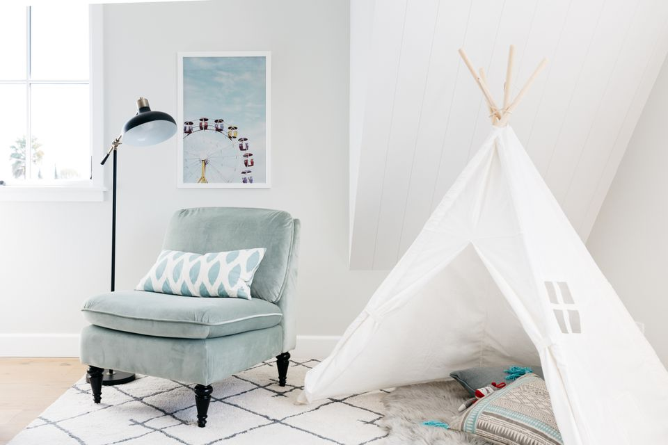 White teepee set up in kids bedroom next to light green chair and lamp with white walls surrounding