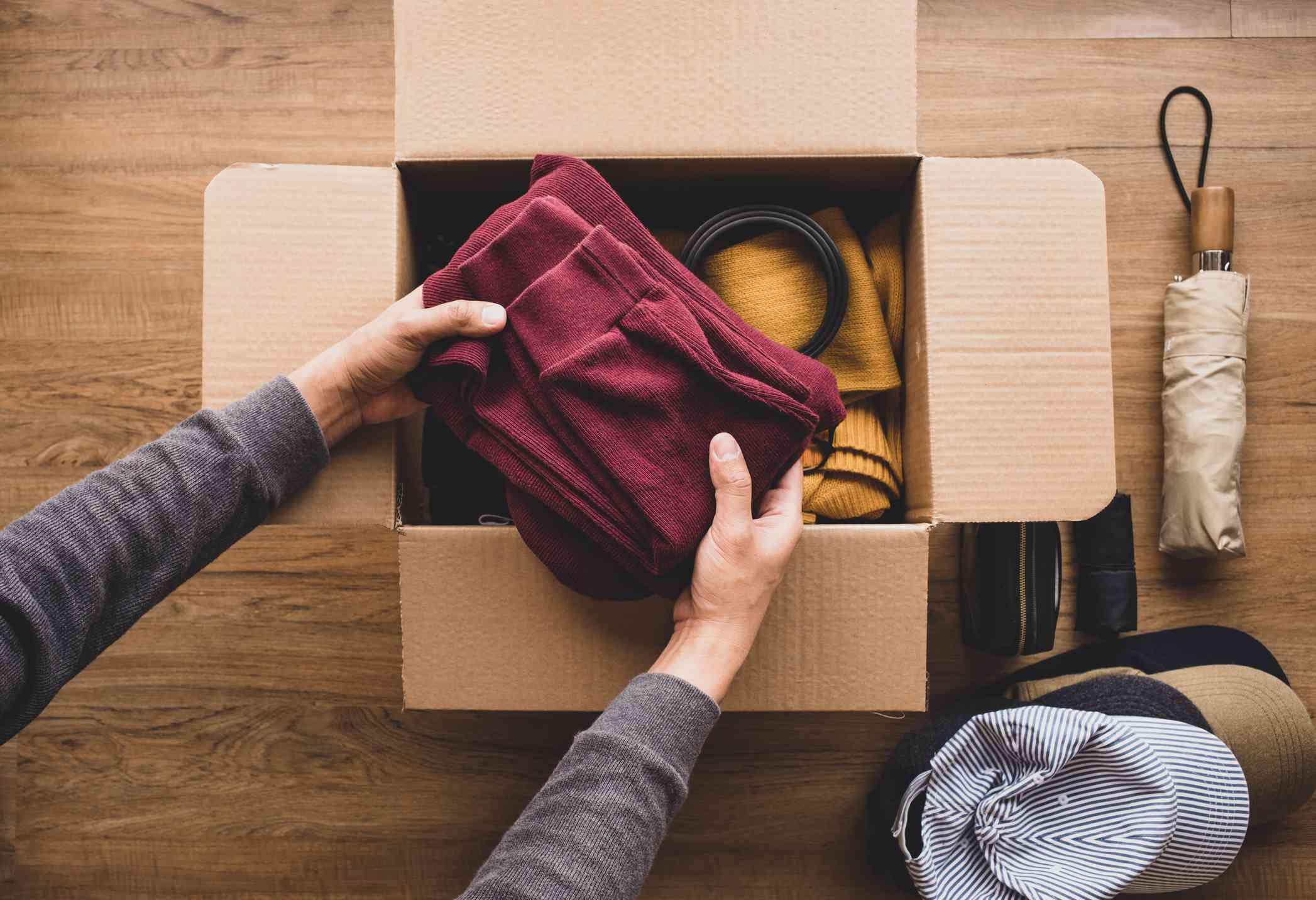 Limpieza del hogar y conceptos de donación con jóvenes persona que pone ropa de accesorios en una caja marrón. entrega y compartir con humanos