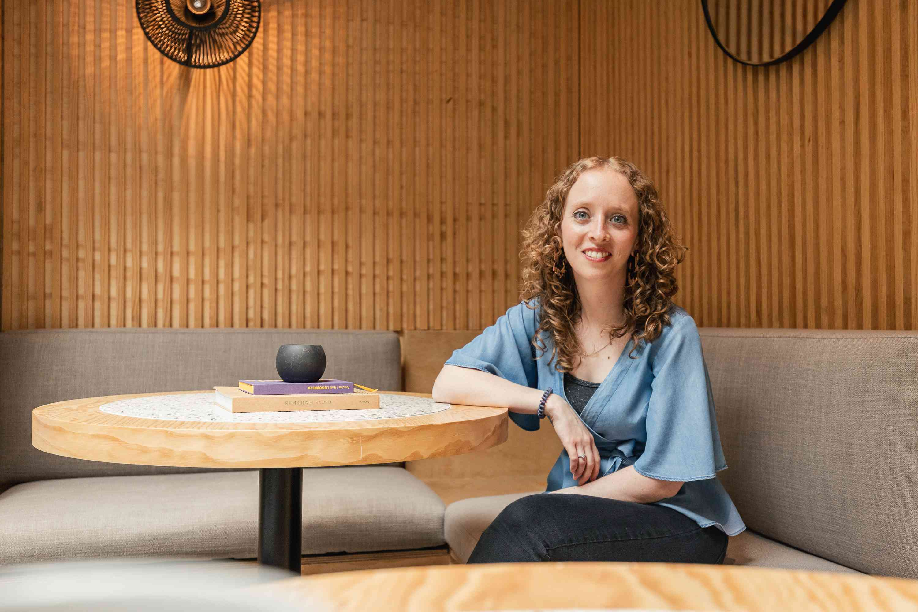 Alexa Backel poses at a wooden table with a textured wall in the background