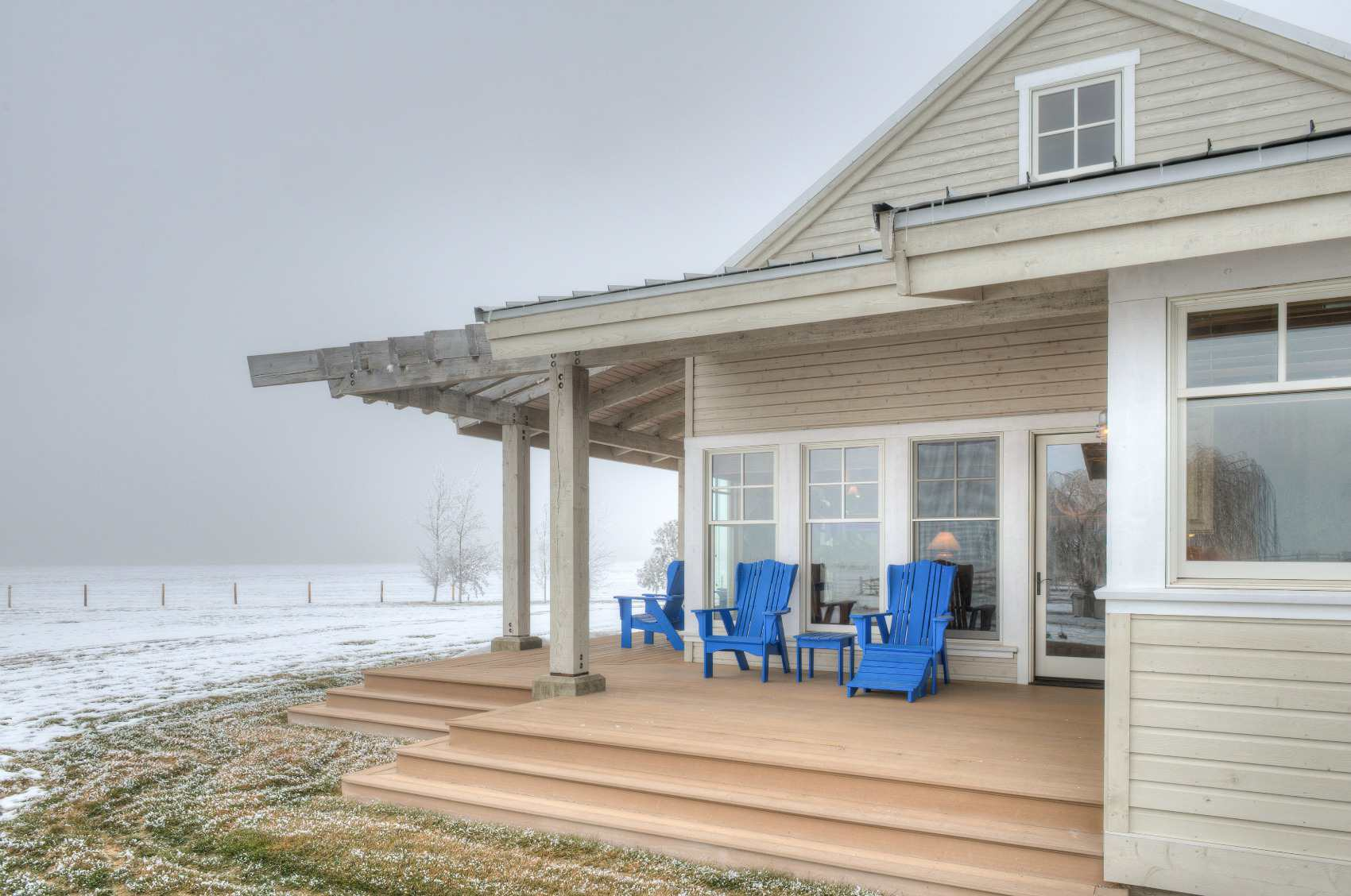 Covered deck attached to house with blue chairs
