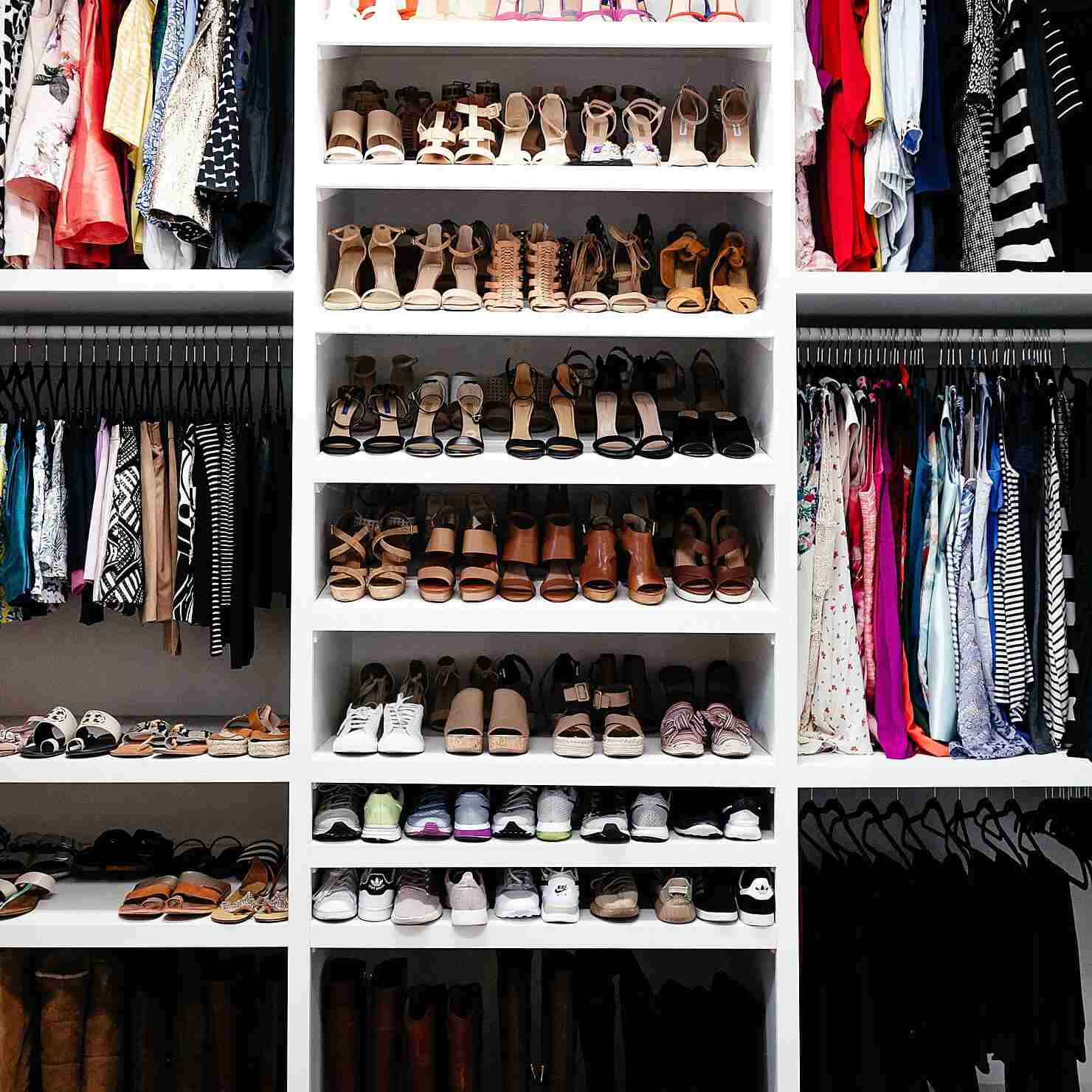 organized closet with shelves of shoes and nooks with shirts hanging on bars
