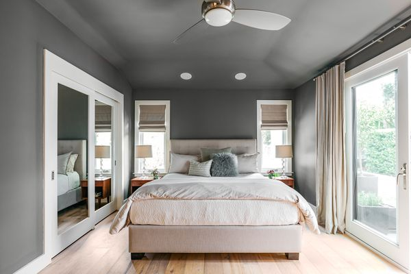 Bedroom with gray painted ceiling and walls with made bed in middle
