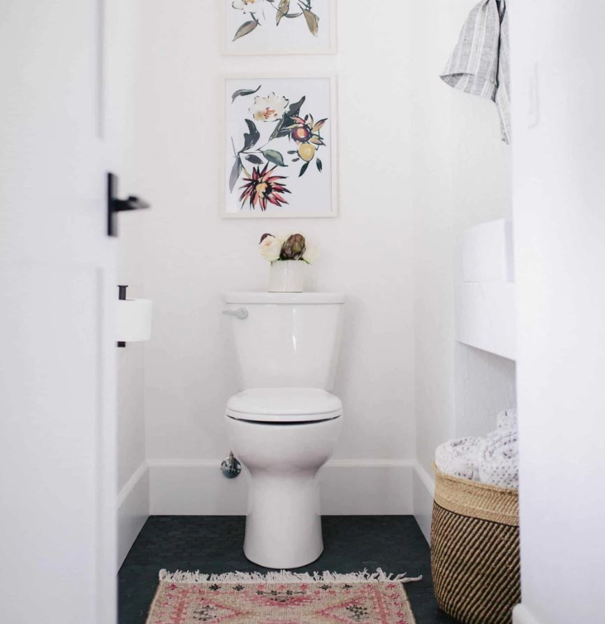 Remodeled powder room with white walls, black floor, and floral art.