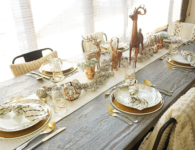 Long table with gold placesetts and reindeer centerpieces.