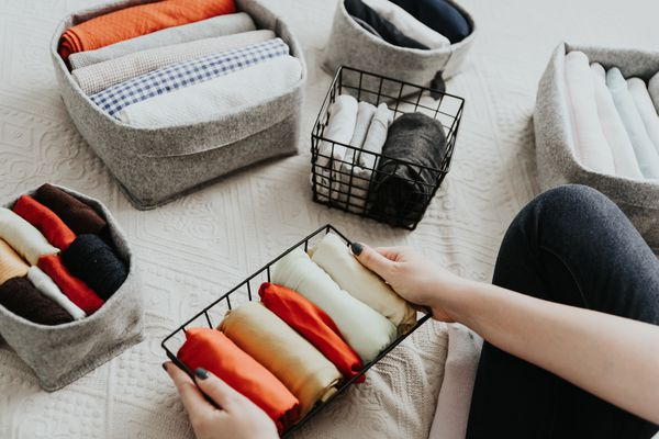 Person organizing home items into baskets and bins