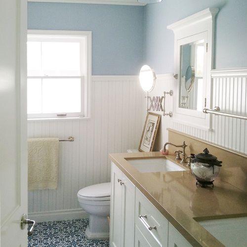 A beadboard bathroom with light blue wall paint and a blue tile floor