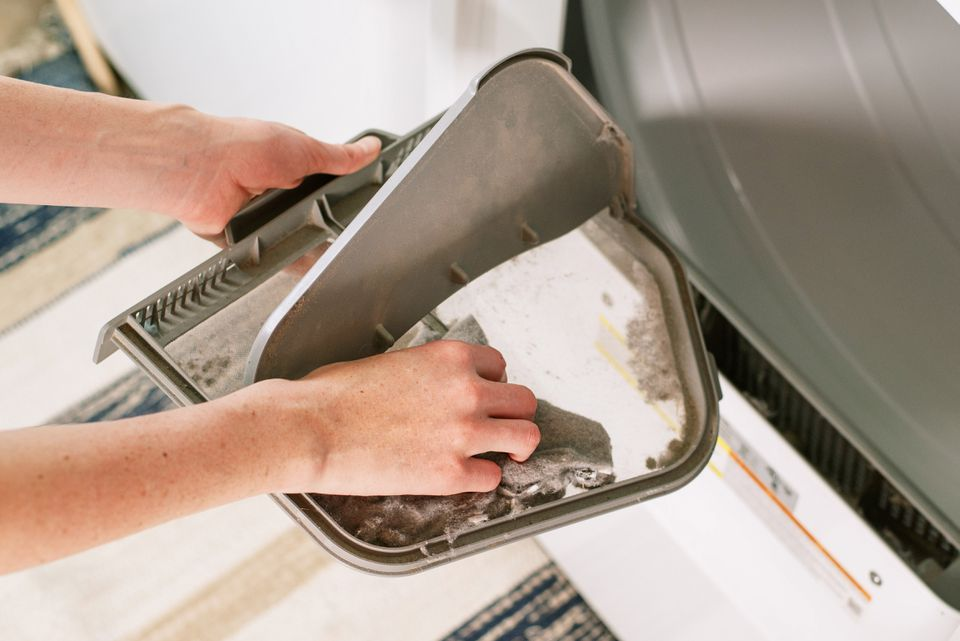 Dryer lint being removed from dryer filter by hand