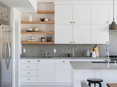 White kitchen cabinets with gray countertops and wooden shelves