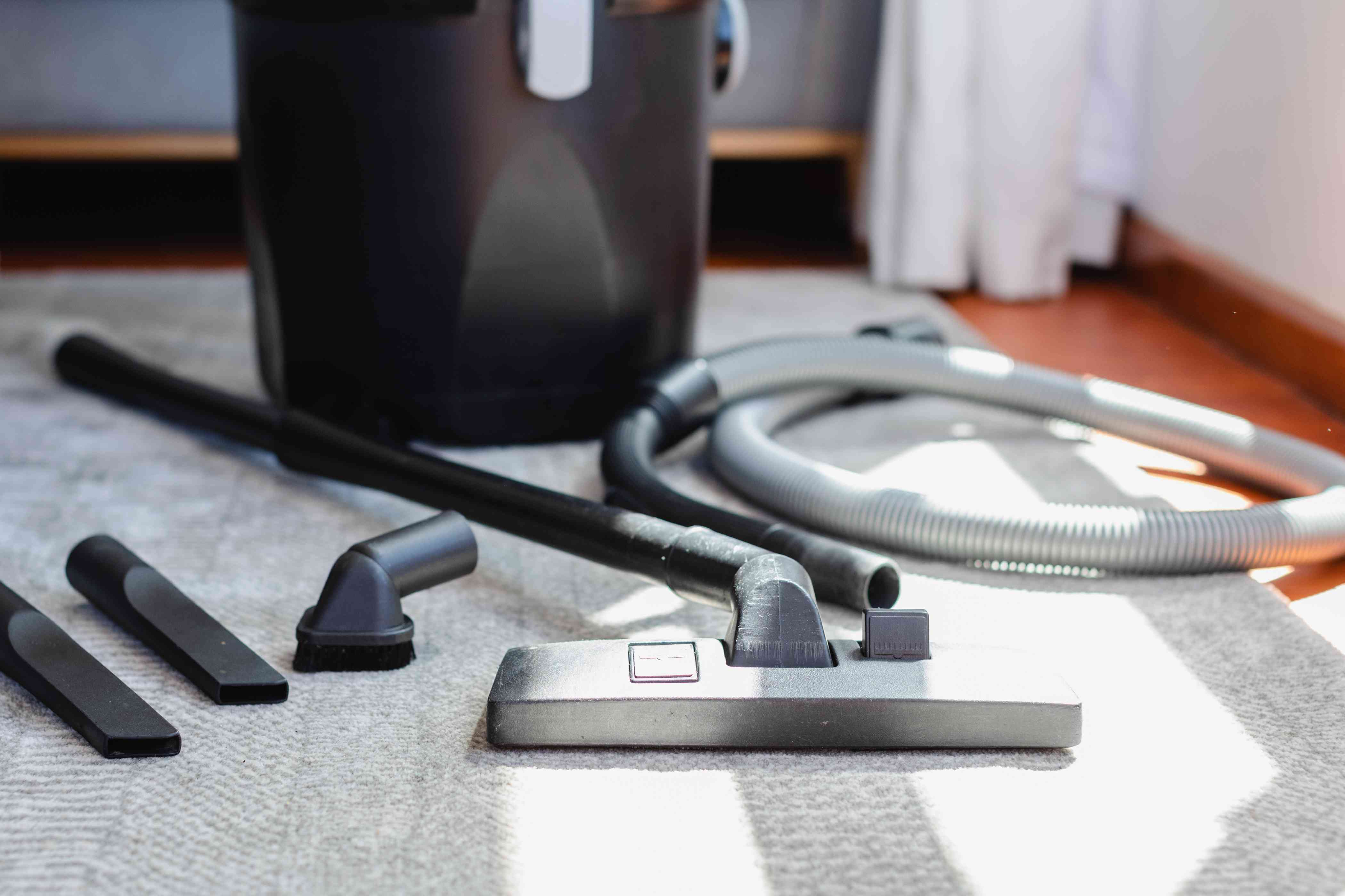 Upright vacuum cleaner with hose adjustments laid on carpet