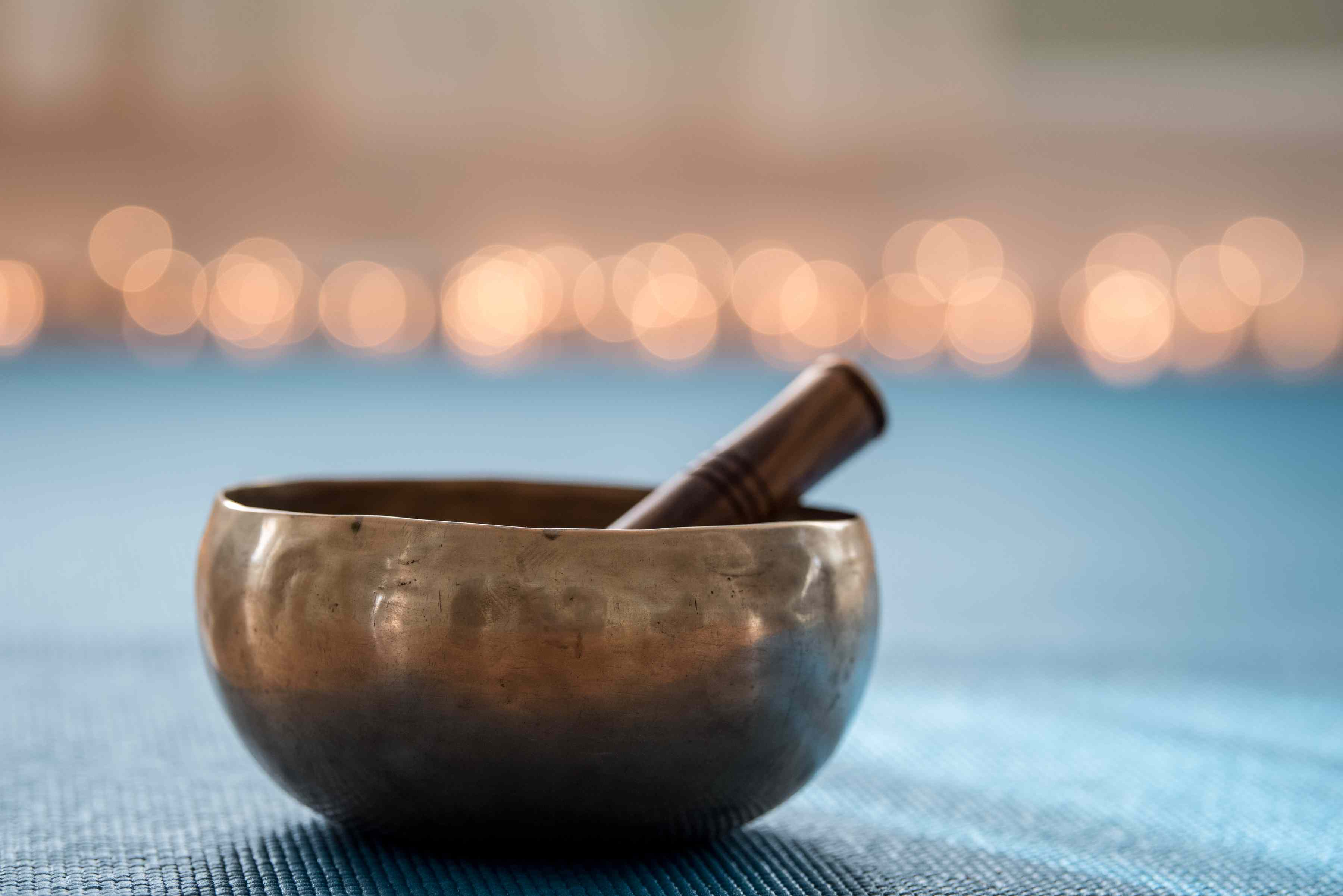 Tibetan singing bowl (musical instrument) on yoga mat with lights in background