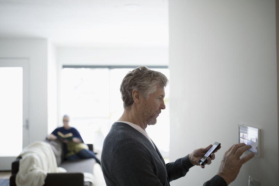 man using smart phone to adjust heat