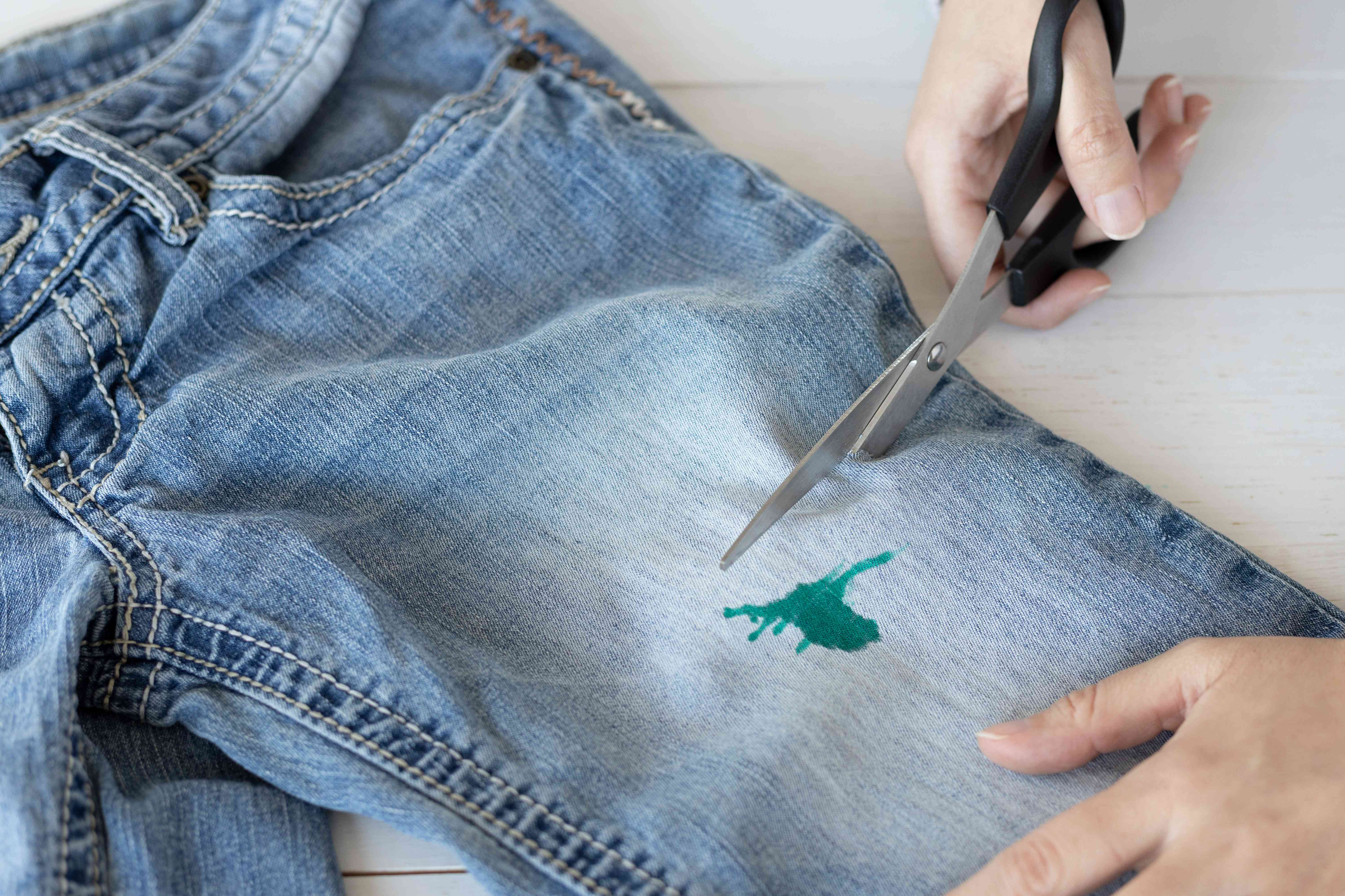 Jeans with green stain being cut off by scissors