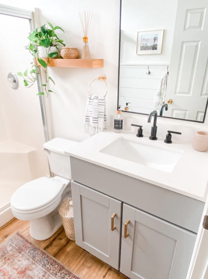 Updated bathroom with gray vanity, white walls, and wood floor.