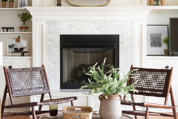 White living room with fireplace, plants and minimal decor