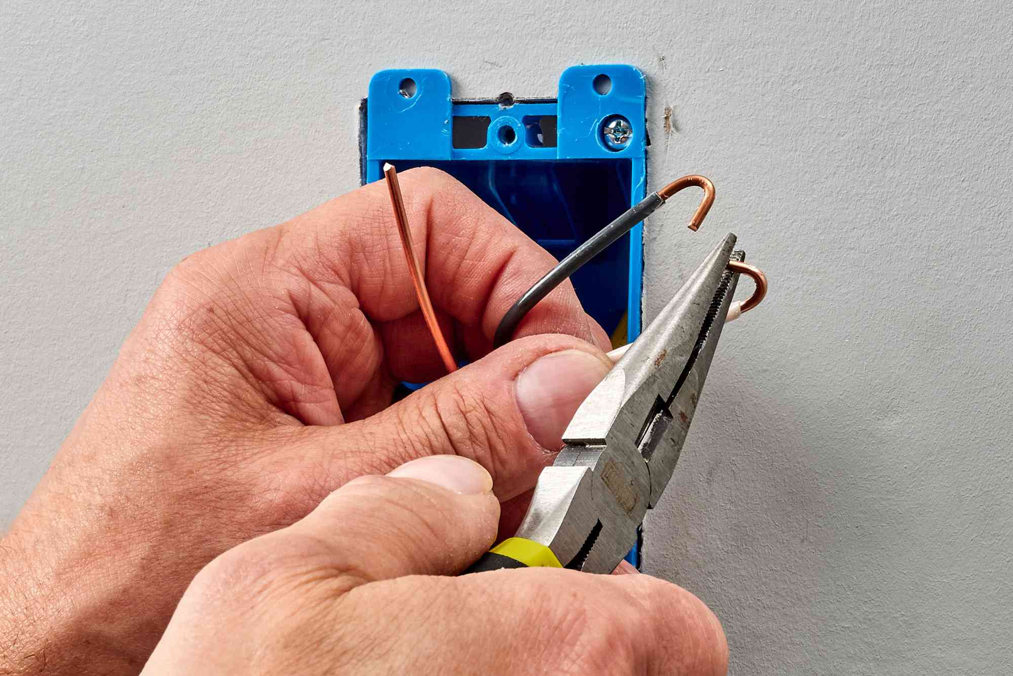 Wire bending into a hook shape with needlenose pliers